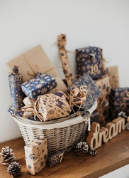 Christmas Advent calendar for kids. Basket with gift boxes with numbers and tasks for children standing on cabinet