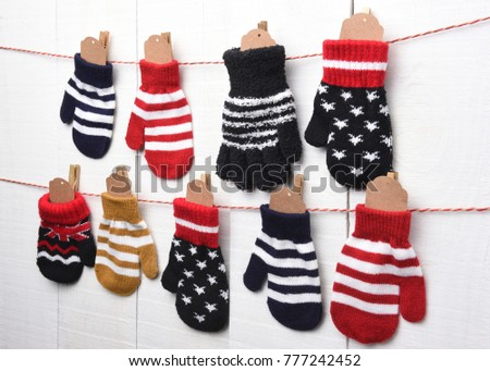 Christmas Advent Calendar: Mitten and Gloves hanging on string and clothes pins against a white wall. Blank tags are in the mittens ready for your copy.