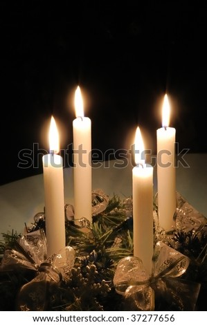 Christmas advent wreath with burning candles laid on table with black background