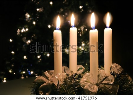 Christmas advent wreath with burning candles. Lights on x-mas tree in background