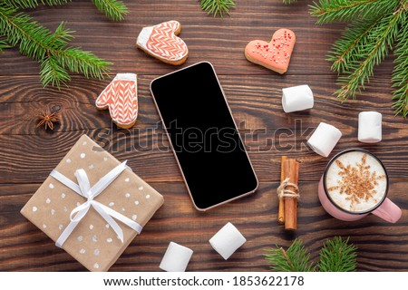 Photo of  Christmas ambience with Mockup of smartphone and present on wooden background. Flat lay top view.