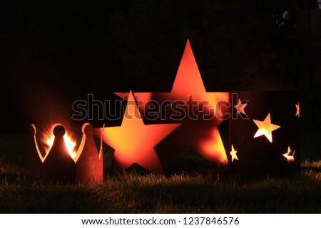 Christmas and advent atmosphere at night with stars, candles, fire, a crown and a lantern with a black blurry background. Close up.
