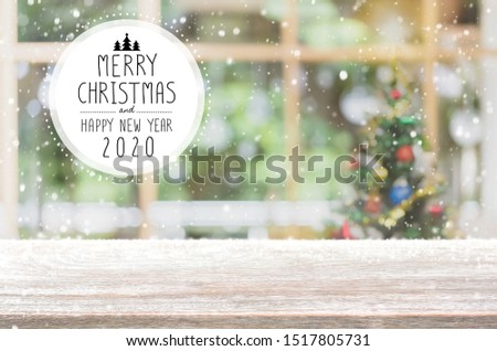 Christmas and Happy new year 2020 on empty wood table top on blur bokeh christmas tree background with snowfall - can be used for display or montage your products. #1517805731