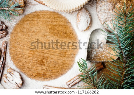 Christmas and holiday baking, cookies, flour, spruce branches and round space for text on a wooden board, ready template
