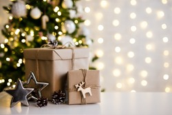 christmas and new year background - gift boxes and stars near decorated christmas tree and copy space over white wall with garland lights