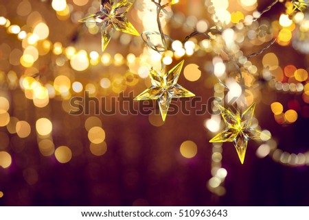 Christmas and New Year Background with Holiday Decoration garland, tinsel and stars. Abstract Blurred Bokeh Holiday Backgdrop. Blinking Garland. Christmas Tree Lights Twinkling