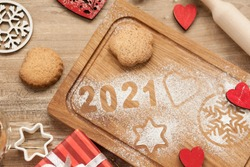 Christmas and New Year 2021 background with ingredients for cooking christmas baking decorated with fir tree. New Year's decor, homemade cookies  preparing for the holiday.