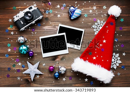 Christmas and New Year background with old fashioned camera, red Santa's hat, photo frames and christmas decorations - stars, silver snowflakes, confetti on wooden table. Place for your text. Mock up.