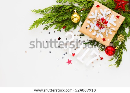 Christmas and New Year 2017 background with thuja branch, decorations and present wrapped in craft paper with snowflakes. Flat lay, top view. Place for text. #524089918