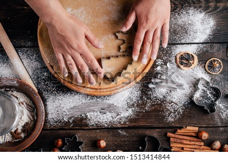 Christmas and New Year celebration traditions. Family home bakery, cooking traditional festive sweets. Woman cutting cookies of raw gingerbread dough stock photo