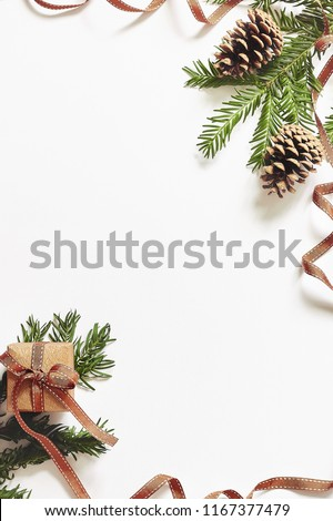 Christmas and New Year composition. Gift box with ribbon and fir branches with cones on white background. Flat lay, top view, copy space for text, vertical