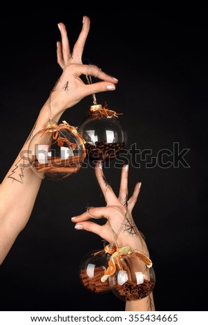 christmas and new year concept hands holding small magic gift balls with aromatic spices inside