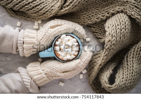 Christmas and New Year cozy holiday composition with scarf, woman hands in mittens, mugs with cocoa or chocolate, marshmallow on the gray concrete background. Flat lay, top view #754117843