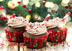 Christmas and New Year cupcakes - chocolate cakes with cream, sprinkles and peppermint candy cane bites decorated for holiday dinner, sweet treats for kids