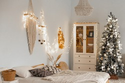 Christmas and New Year decorated interior room. Beautiful holdiay decorated room with bed