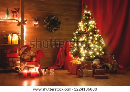 Stock Photo Christmas and New Year decorated interior room. Holiday decorated room with bed on window sill. Festive Xmas night with lights on tree with presents. Magic night with gifts