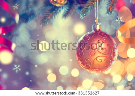 Christmas and New Year Decoration. Golden Bauble hanging on Christmas Tree. Holiday Glowing Background. Shallow DOF