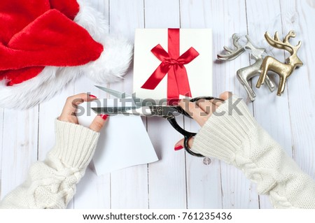 Christmas and New Year gift. Woman holding Christmas presents on a wooden table background #761235436