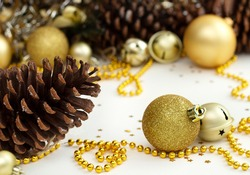 Christmas and New Year holiday background with decorations and beads. Gold shining balls, fir cones, jingle bells and star confetti. Background for greeting card