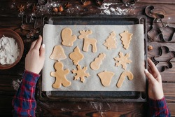 Christmas and New Year holidays, family celebration traditions. Mother cooking festive homemade sweets. Woman holding oven-tray with raw gingerbread cookies before baking