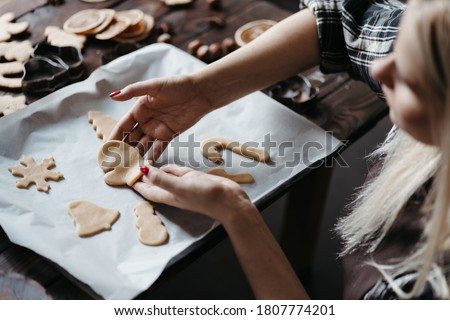Christmas and New Year holidays, family weekend activities, celebration traditions. Mother cooking festive homemade sweets. Woman cutting cookies of raw gingerbread dough stock photo
