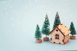 Christmas and New Year miniature  house with fir trees on blue background. Copy space for text. Winter card. Holiday and celebration concept.