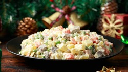 Christmas and New year Olivier salad, traditional Russian food with decoration, gifts, green tree branch on wooden rustic table