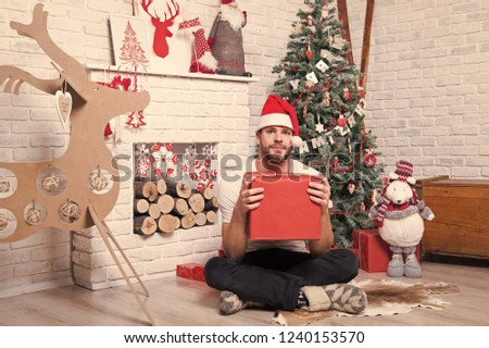 4536163affa50 Christmas and new year presents preparation. Man in santa hat sit on floor  at fireplace