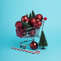 Christmas and New Year shopping layout made with trolley, tree, candy cane and ornaments on bright blue background. Minimal winter December sale or shopping mall concept.