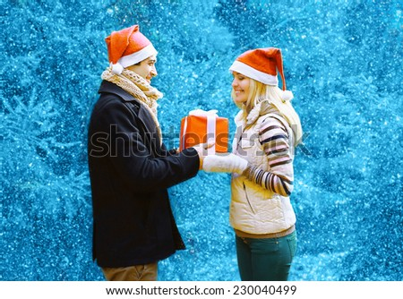 Christmas and people concept - happy man giving a box gift to a woman, happy pretty couple in winter snowy day