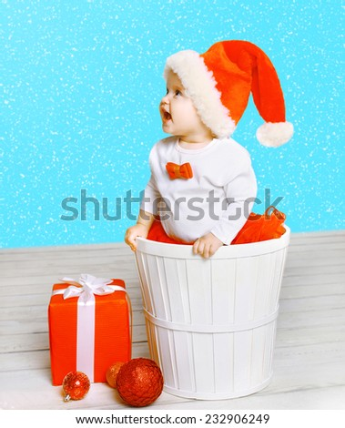 Christmas and people concept - joyful positive child in santa hat with gifts against the snowflakes
