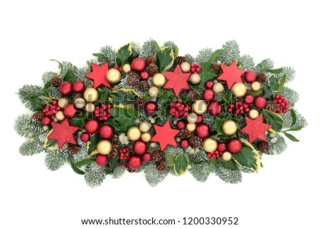 Christmas and winter table decoration with red and gold bauble decorations, holly berries, spruce pine, ivy, pine cones and mistletoe isolated on white background.