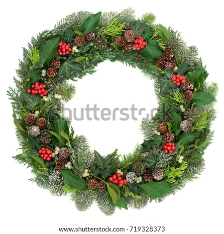 Christmas and winter wreath decoration with holly, mistletoe, juniper fir, blue spruce, cedar, pine cones and ivy leaves on white background. #719328373