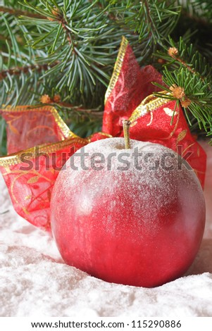 Christmas apple with a ribbon in the snow.