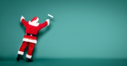 Christmas are coming! Real Santa Claus is getting ready for the season, painting the wall.