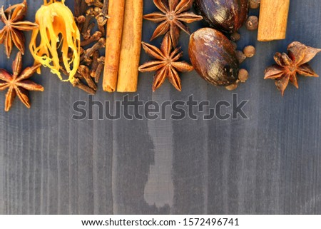Christmas aromatic spices on wooden background. Food ingredients: star anise, nutmeg, cinnamon sticks, allspice and cloves. #1572496741