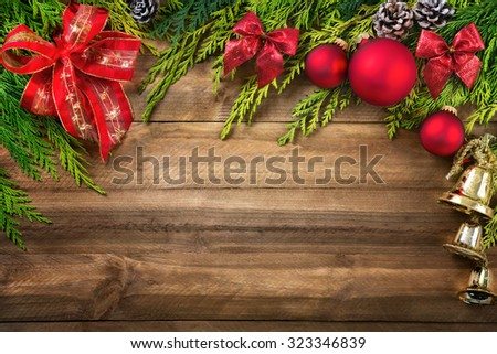 Christmas arrangement with conifer branches, red bows and baubles, pine cones and gold bells bordering a rustic wood planks background