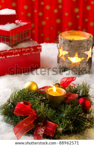 Christmas arrangement with wreath, balls, candles and gift boxes, covered with snow