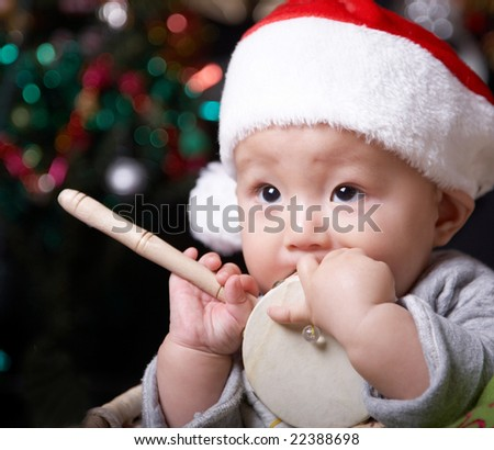 christmas baby holding a toy drum.