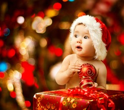 Christmas Baby in Santa Hat, Child holding Red Ball near Present Gift Box over Holiday Lights background
