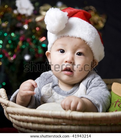 christmas baby on black background with colorful lights.