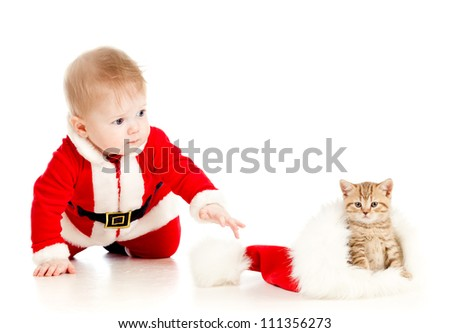 christmas baby reaching out hand for cat in a santa claus hat