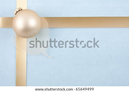 Christmas back ground with gold ribbon on light blue with a golden ball at the left