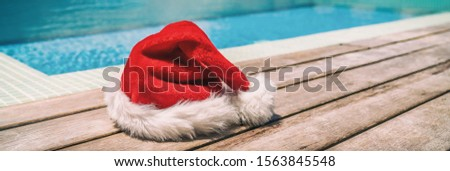 Christmas background banner santa claus red hat on swimming pool vacation holiday resort horizontal header for south holidays winter vacations.