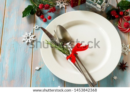 Christmas background. Christmas decoration table. Festive white plate and cutlery with Christmas decor on retro wooden table. Free space for your text. #1453842368