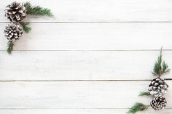 Christmas background. Christmas frame made of fir leaves and pine cones decoration rustic elements on white wood board. Creative flat lay, top view design