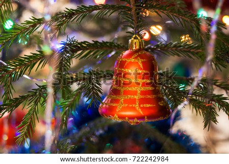 Christmas background. Close-up christmas toy red bell, painted with gold, is hanging on the fir tree. #722242984