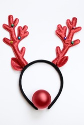 Christmas background concept. Top view funny Christmas antlers of a deer and a red ball as a nose isolated on white background