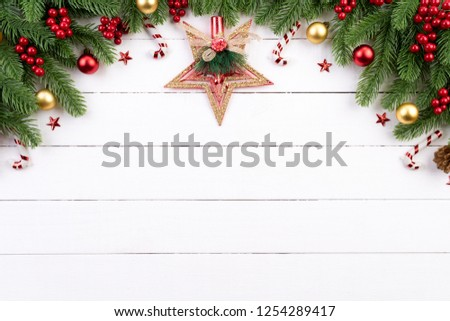 Christmas background concept. Top view of Christmas gift box red balls with spruce branches, pine cones, red berries and bell on white wooden background. #1254289417