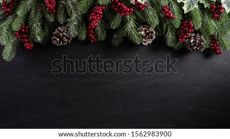 Christmas background concept. Top view of Christmas gift box red balls with spruce branches, pine cones, red berries and bell on black wooden background.